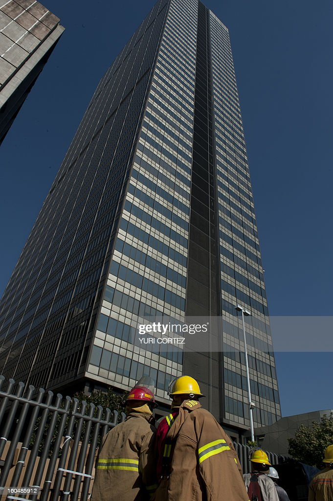 Firefighters stare at the building that houses the headquarters of the state-owned Mexican oil giant Pemex, following a blast on the eve, in Mexico City on February 01, 2013. An explosion rocked the skyscraper, leaving up to 32 dead and 121 injured. Hundreds of firefighters, police and soldiers toiled through the night after the blast ripped through an annex of the 54-floor tower leaving concrete, computers and office furniture strewn on the ground. AFP PHOTO/YURI CORTEZ