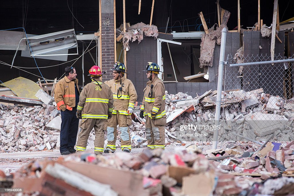 Firefighters stood amongst the rubble at the scene of a natural gas explosion that leveled Scores Gentleman's Club and damaged several nearby buildings on Worthington Street in Springfield.