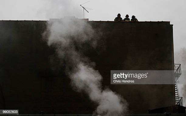 Firefighters supervise from a rooftop as their comrades douse a threealarm fire that broke out at 502 East 14th Street across from Stuyvesant Town in...