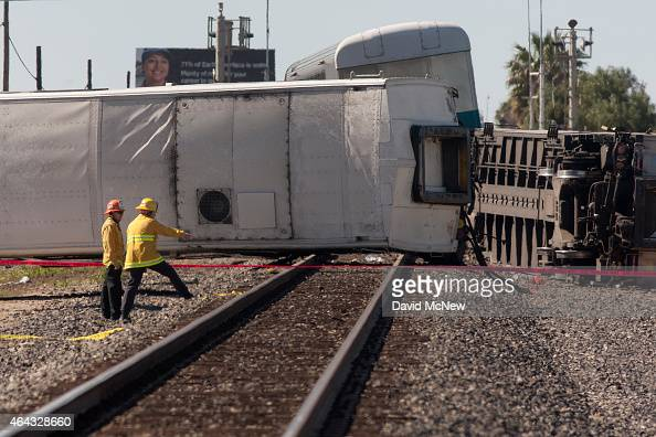 Firefighters survey the wreckage of a Los Angelesbound Metrolink train that derailed in a fiery collision with a truck on the tracks on February 24...