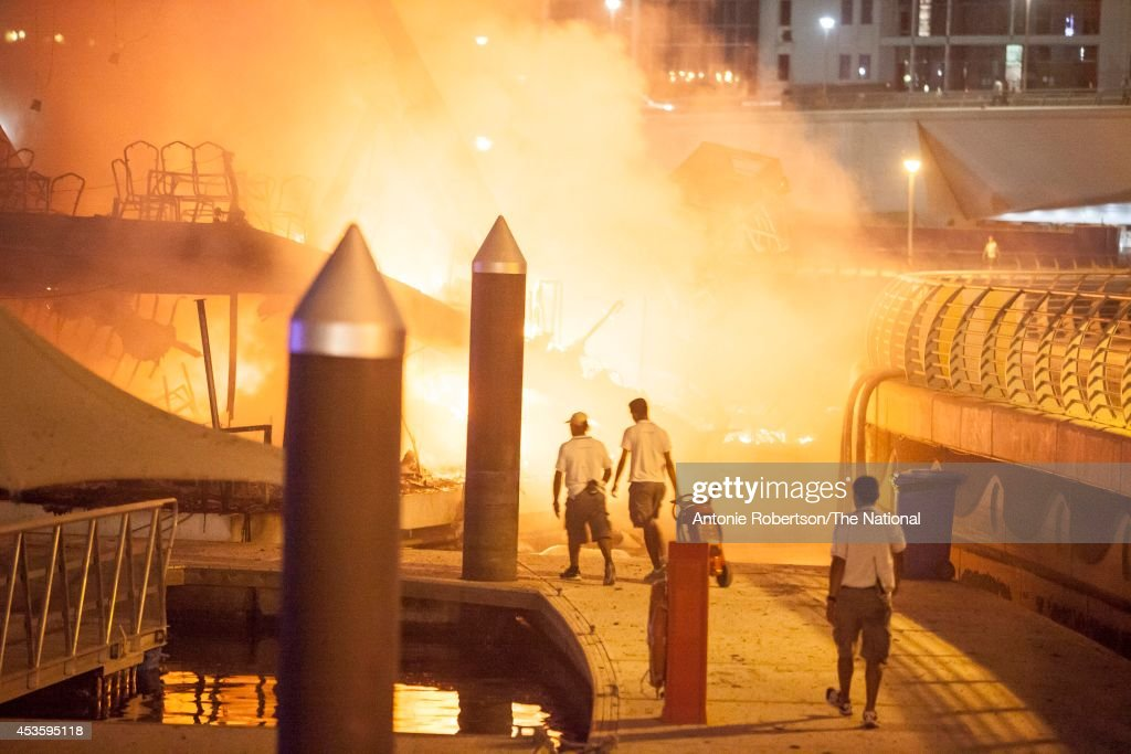 Firefighters tackle a boat ablaze, moored near Al Rahim Mosque in Dubai Marina on August 14, 2014 in Dubai, United Arab Emirates. Passengers were forced to jump out of the boat's windows to escape the flames.