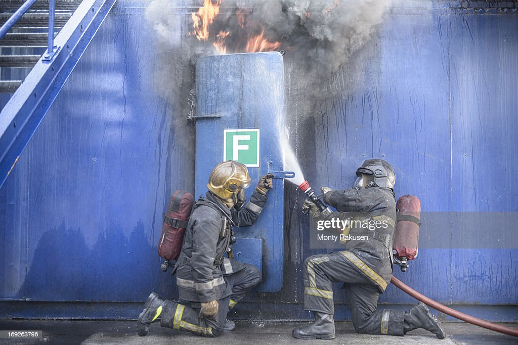 Firefighters tackling flames behind steel door in fire simulation training facility : Stock Photo