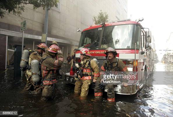 Firefighters take a break after coming out of a store that is on fire on Canal Street August 31 2005 in New Orleans Louisiana Devastation is...