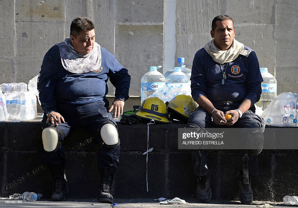 Firefighters take a rest during works at the premises of the building that houses state-owned Mexican oil giant Pemex following a blast on the eve, in Mexico City on February 01, 2013. An explosion rocked the skyscraper, leaving up to 32 dead and 121 injured. Hundreds of firefighters, police and soldiers toiled through the night after the blast ripped through an annex of the 54-floor tower leaving concrete, computers and office furniture strewn on the ground. AFP PHOTO/Alredo Estrella