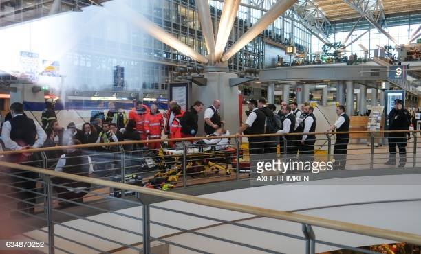 Firefighters take care of a person on a stretcher inside Hamburg airport on February 12 2017 in Hamburg northern Germany as German emergency services...