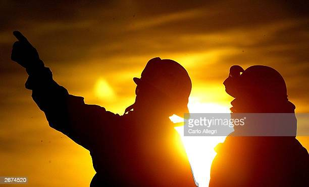 Firefighters talk while they battle the Crestline Wildfire that has swept through the area in Los Angeles County October 28 2003 near Los Angeles...