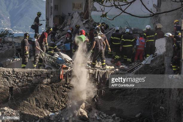 Firefighters throw away the debris of a collapsed building on the binaries of the railway after two floors collapsed in a small fourstorey building...