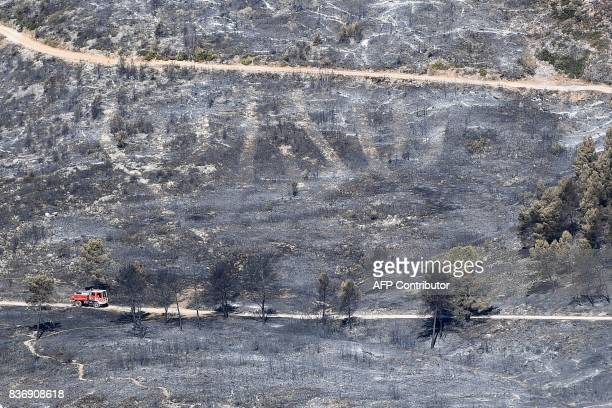 TOPSHOT A firefighters truck drives on a road in a blackened and devastated area following a fire on August 22 2017 in CarnouxenProvence southeastern...