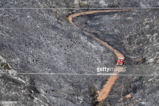 A firefighters truck drives on a road in a blackened and devastated area following a fire on August 22 2017 in CarnouxenProvence southeastern France...