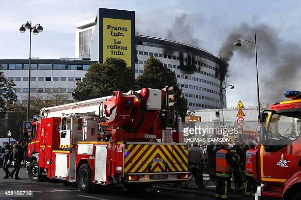 Firefighters trucks are parked in a street near the Maison de la Radio as smoke billows from the building hosting the Radio France stations during a...