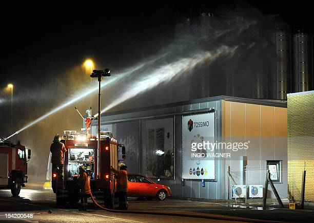 Firefighters try to contain toxic gases with water at a plant of Kraft Foods in Bad Fallingbostel northern Germany on October 16 2012 Catastrophe...