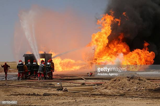 Firefighters try to exFlames rise over the Habbaza oilwells after the oilwells were sabotaged last month in Kirkuk Iraq on June 2 2016 The fire at...