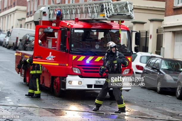 Firefighters try to extinguish a fire at an apartment building in the Maurice Berteaux street in Paris on January 6 2016 / AFP PHOTO / KENZO...