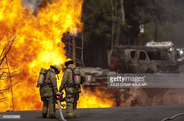 Firefighters try to extinguish a fire caused by the explosion of a gas pipeline after the collapse of an underconstruction building in Monterrey...