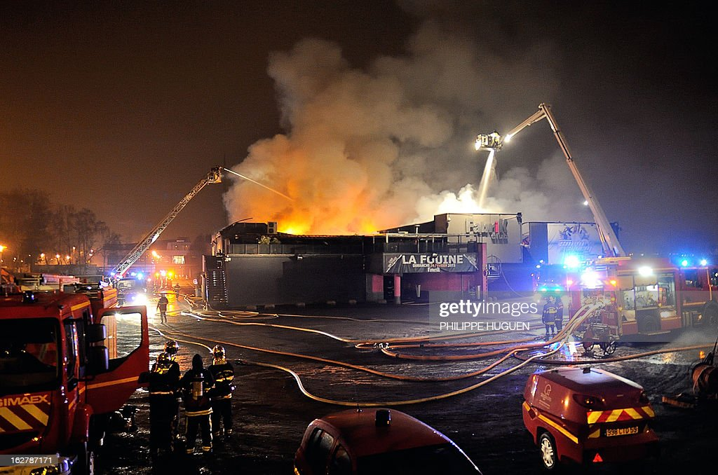 Firefighters try to extinguish a fire on February 27, 2013 that swept through the nightclub 'La Fabrik' in Villeneuve d'Ascq in a suspected arson attack. A car was used to smash the door before the fire was set.