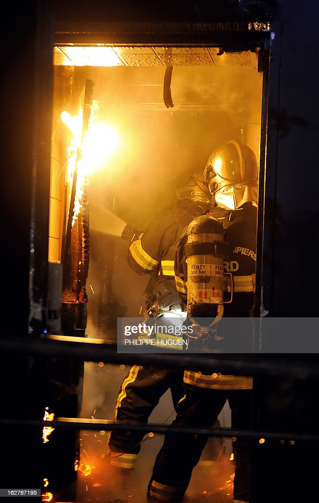 Firefighters try to extinguish a fire on February 27, 2013 that swept through the nightclub 'La Fabrik' in Villeneuve d'Ascq in a suspected arson attack. A car was used to smash the door before the fire was set. AFP PHOTO PHILIPPE HUGUEN