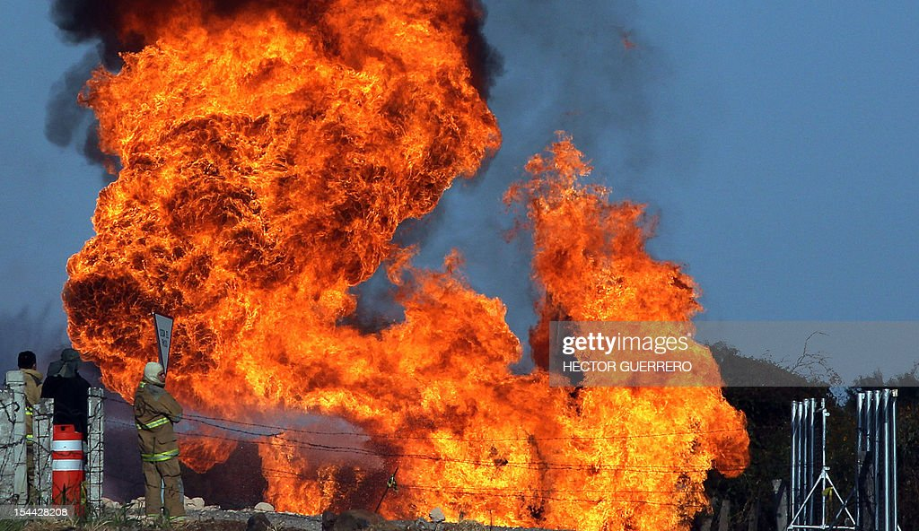 Firefighters try to extinguish fire after a gas pipeline explosion in Zapotlanejo, 30 km from Guadalajara city, Jalisco State, Mexico on October19, 2012. A leaking gas pipeline exploded in western Mexico, forcing the evacuation of 2,000 people, and injuring at least three, as crews battled Friday to put out the blaze. The fire broke out Thursday evening in the town of Zapotlanejo near a highway and forced authorities to close the road, said Trinidad Lopez Rivas, head of the emergency services department in Jalisco state. AFP PHOTO/Hector Guerrero