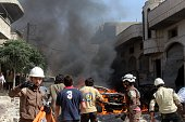 Firefighters try to extinguish fire after a helicopter belonging to Syrian army carried out attacks to Al Bara village of Idlib in Syria on June 14...