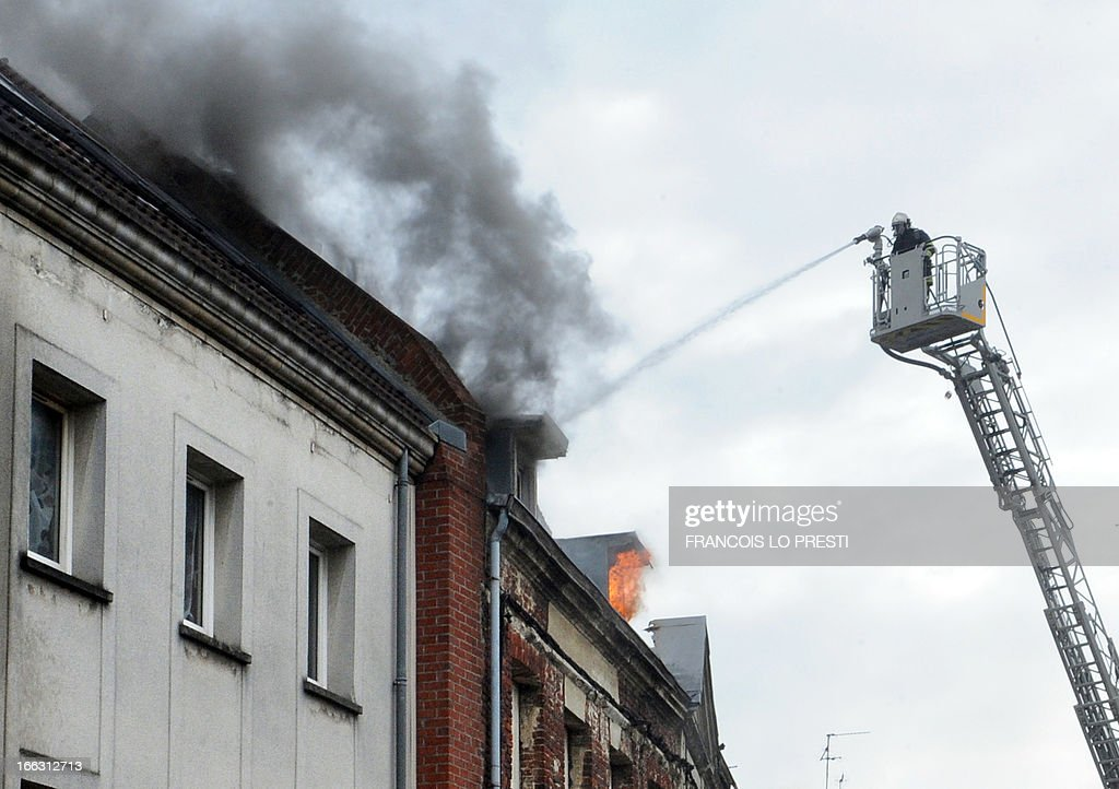 Firefighters try to extinguish fire of a printing house on April 11, 2013 in the town centre of Valenciennes, northern France. One hundred people were evacuated today, and two people were slightly injured, according to firefighters. AFP PHOTO / FRANCOIS LO PRESTI