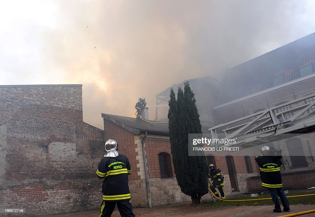 Firefighters try to extinguish fire of a printing house on April 11, 2013 in the town centre of Valenciennes, northern France. One hundred people were evacuated today, and two people were slightly injured, according to firefighters.