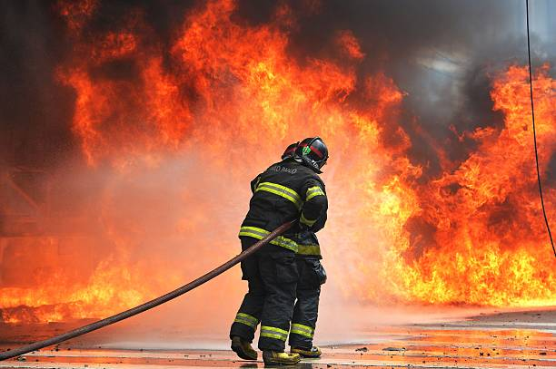 Firefighters Try To Extinguish The Fire On A Bus Set Ablaze During Clashes Between Riot