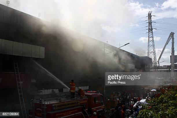 Firefighters trying to extinguish a fire that burns shopping center Pasar Senen Jakarta The fire was reported at 445 am and has been no report on the...