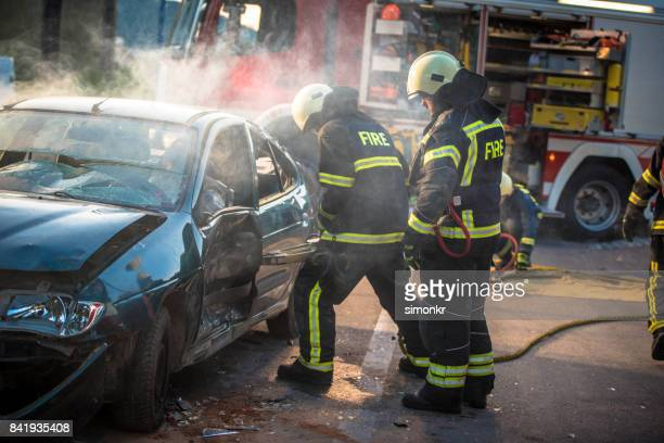Firefighters trying to open car door