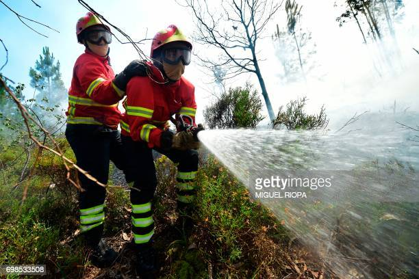 TOPSHOT Firefighters use a hose as they combat a wildfire in Vale da Ponte Pedrograo Grande on June 20 2017 The huge forest fire that erupted on June...