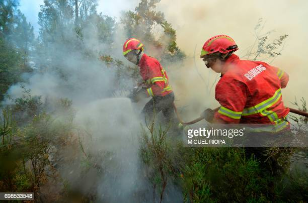 Firefighters use a hose as they combat a wildfire in Vale da Ponte Pedrograo Grande on June 20 2017 The huge forest fire that erupted on June 17 2017...