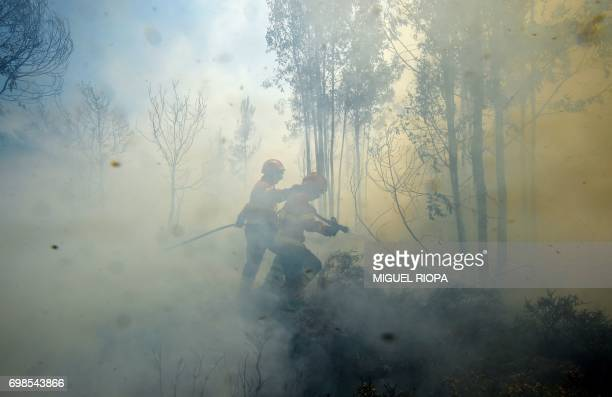 TOPSHOT Firefighters use a hose to combat a wildfire in Vale da Ponte Pedrograo Grande on June 20 2017 The huge forest fire that erupted on June 17...
