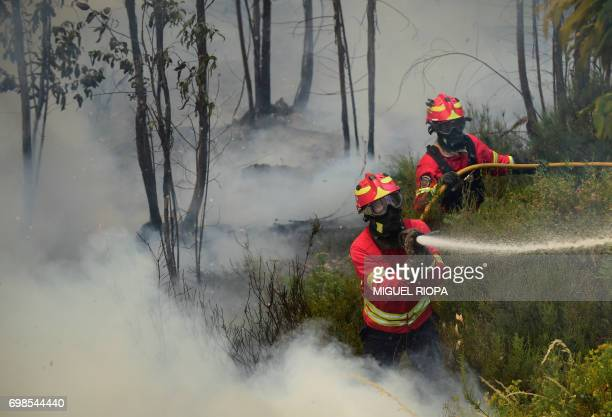 Firefighters use a hose to combat a wildfire in Vale da Ponte Pedrograo Grande on June 20 2017 The huge forest fire that erupted on June 17 2017 in...