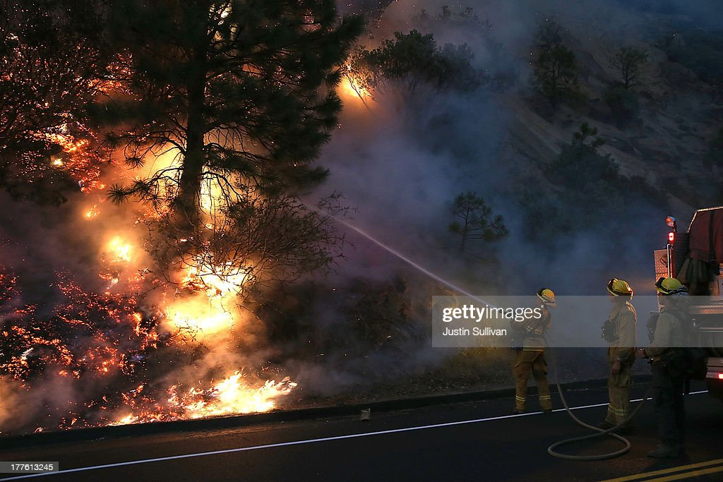 Firefighters use a hose to douse the flames of the Rim Fire on August 24, 2013 near Groveland, California. The Rim Fire continues to burn out of control and threatens 4,500 homes outside of Yosemite National Park. Over 2,000 firefighters are battling the blaze that has entered a section of Yosemite National Park and is currently 5 percent contained.