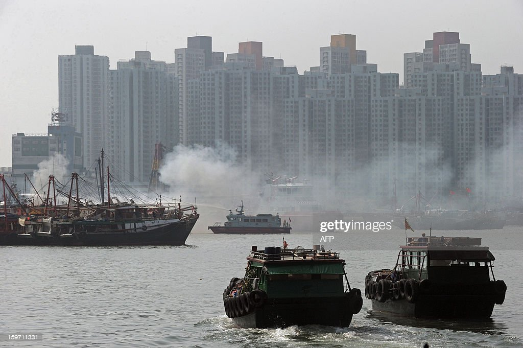 Firefighters use a water cannon on a fire boat (C) to extinguish the flames coming from two fishing vessels in Hong Kong on January 19, 2013. There were no initial reports of injuries during the incident, which took place in a crowded typhoon shelter. AFP PHOTO / ANTHONY WALLACE