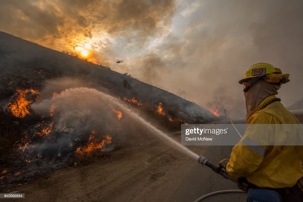 Firefighters use hoses and helicopters to fight the La Tuna Fire on September 2, 2017 near Burbank, California. Los Angeles Mayor Eric Garcetti said at a news conference that officials believe the fire, which is at 5,000 acres and growing, is the largest fire ever in L.A. People have been evacuated from hundreds of homes in Sun Valley, Burbank and Glendale. About 100 Los Angles firefighters are expected to return soon from Texas, where they've been helping survivors from Hurricane Harvey.