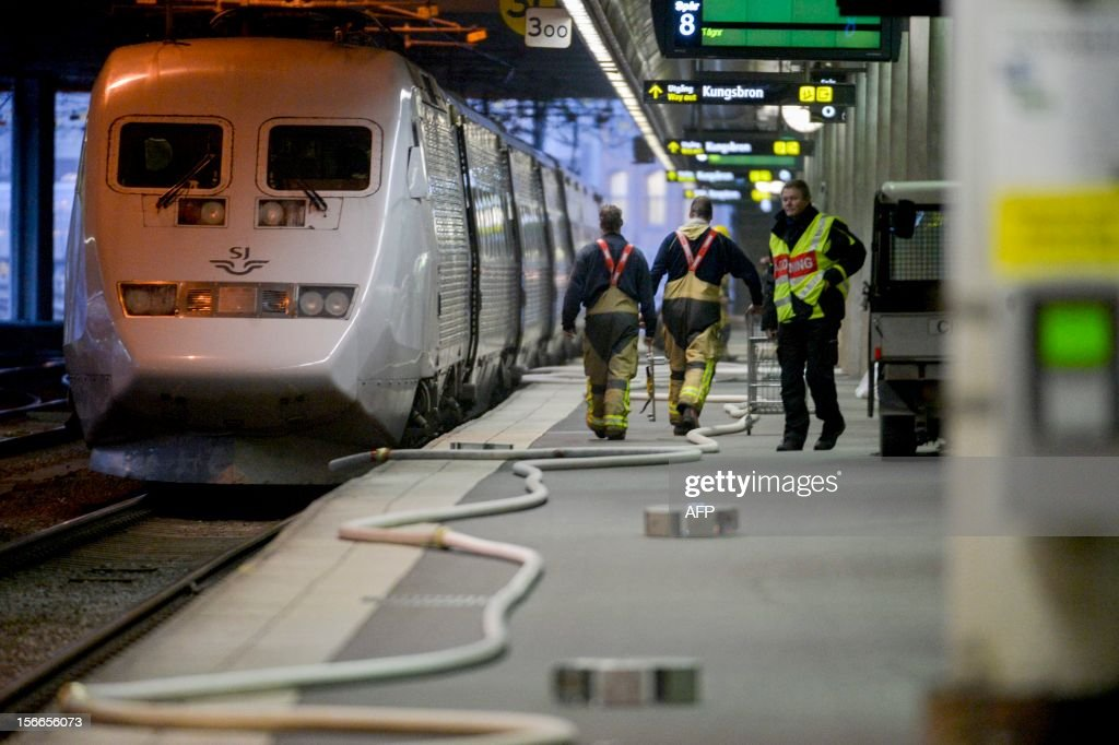 Firefighters walk along an abandoned train at the central station in Stockholm, on November 18, 2012. A fire on board an SJ X2000 train put a halt to all train traffic to and from the city as the station was ecacuated.