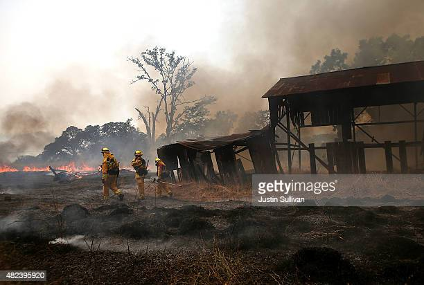 Firefighters walk by an outbuilding that they were able to protect from a back fire while battling the Rocky Fire on July 30 2015 in Lower Lake...