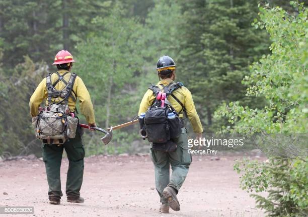Firefighters walk down a dirt road to help fight a wildfire that is burning in the area on June 25 2017 outside Panguitch Utah The fire named the...