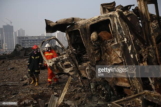 Firefighters walk past a damaged truck at the site of the explosions in Tianjin on August 15 2015 Residents near the site of two giant explosions in...
