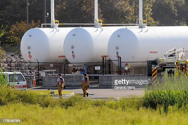 Firefighters walk past propane cylinders on the grounds of Blue Rhino a propane gas company after a series of explosions rocked the central Florida...