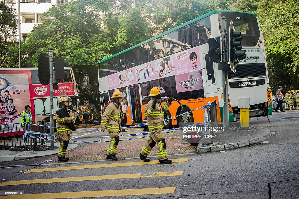 Firefighters walk past two double-decker buses involved in an accident with a taxi in Hong Kong on November 19, 2012. Three people died and about 50 were injured in the crash which occured in the eastern district of Shau Kei Wan. AFP PHOTO / Philippe Lopez