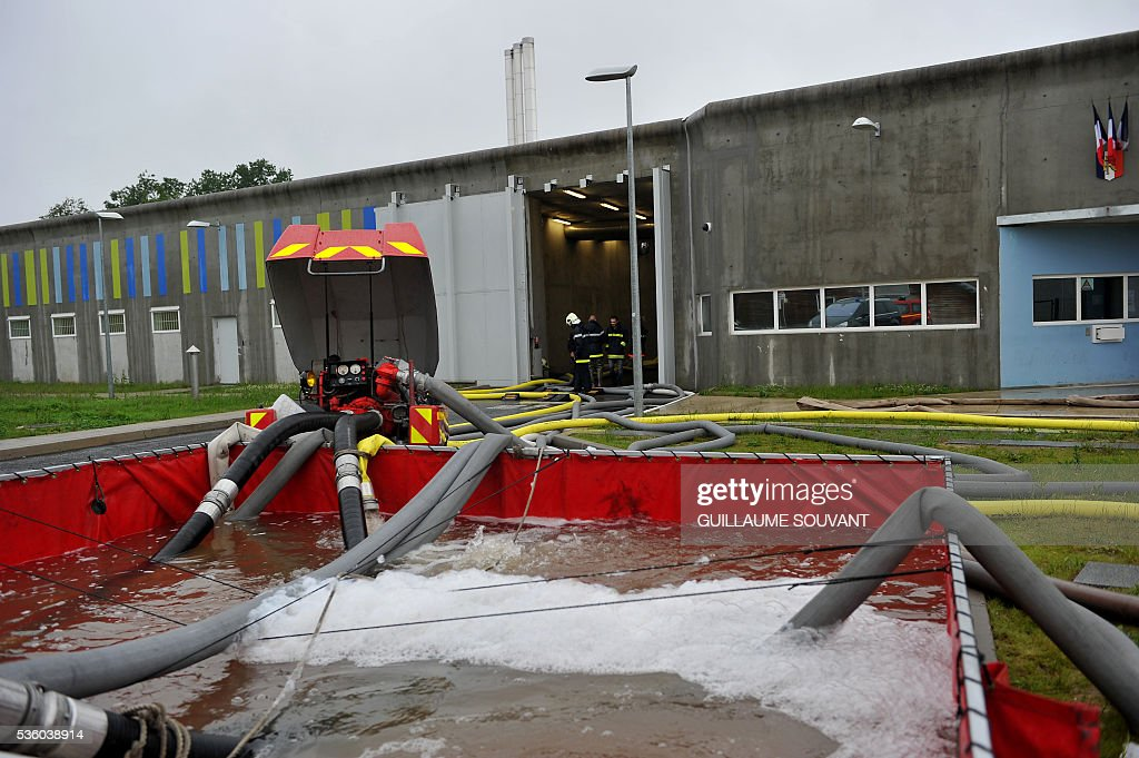 Firefighters walk the entrance of the prison on May 31, 2016 at Saran after heavy rainfalls partly flooded the prison. Some inmates were evacuated to other institutions as the Loiret department is under flood alert and France's weather agency Meteo France maintained on Tuesday 18 departments under orange alert. / AFP / GUILLAUME
