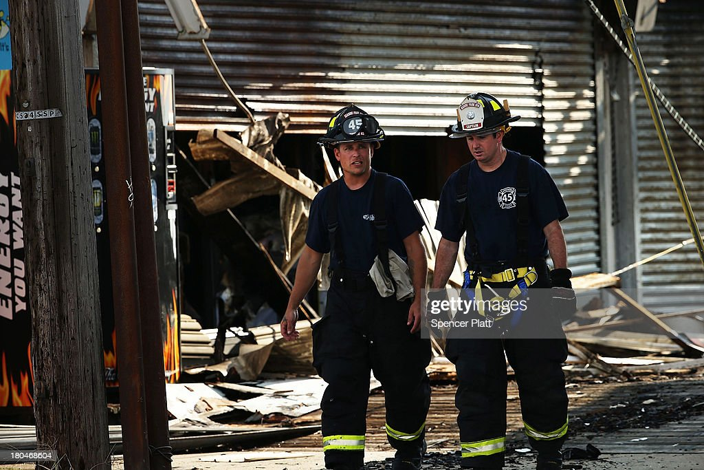 Firefighters walk through the scene of a massive fire that destroyed dozens of businesses along an iconic Jersey shore boardwalk on September 13, 2013 in Seaside Heights, New Jersey. The 6-alarm fire began in a frozen custard stand on the recently rebuilt boardwalk around 2:00 p.m. on Thursday, September 12, and quickly spread in high winds. While there were no injuries reported, many businesses that had only recently re-opened after Hurricane Sandy were destroyed in the blaze.