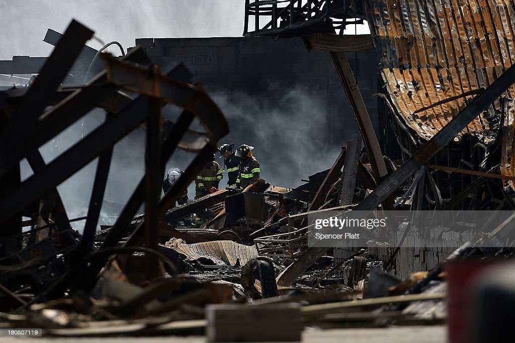 Firefighters walk through the scene of a massive fire that destroyed dozens of businesses along an iconic Jersey shore boardwalk on September 13, 2013 in Seaside Heights, New Jersey. The 6-alarm fire began in a frozen custard stand on the recently rebuilt boardwalk around 2:30 p.m. and quickly spread in high winds. While there were no injuries reported, many businesses that had only recently re-opened after Hurricane Sandy were destroyed in the blaze.