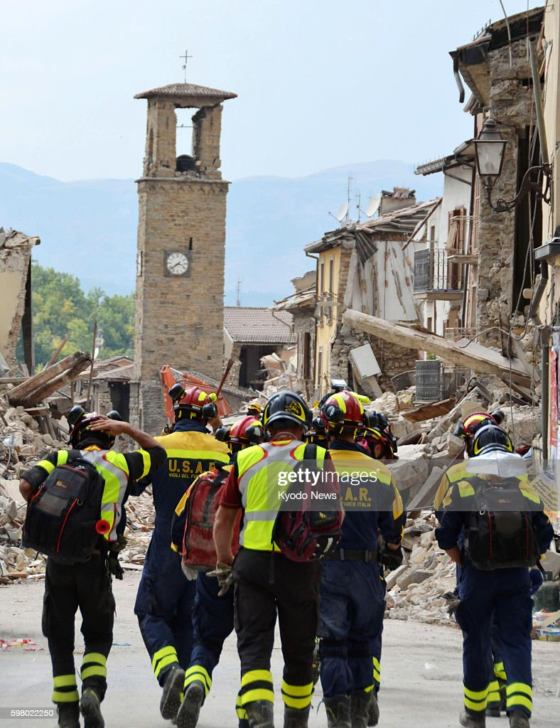 Firefighters walk toward a collapsed building in Amatrice on August 30 2016 in central Italy following a magnitude 62 earthquake that rocked the area...