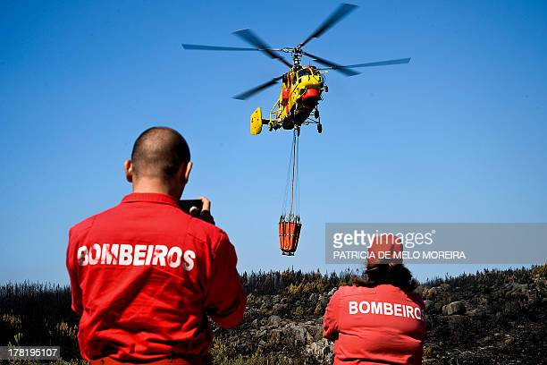 Firefighters watch a firefighter helicopter flying during a wildfire in Alagoa near Oliveira de Frades central Portugal on August 27 2013 AFP PHOTO/...