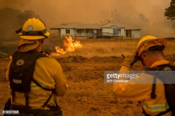 Firefighters watch as flames surround a home in Mariposa California on July 19 2017 The Detwiler fire which has burned more than 45000 acres and...