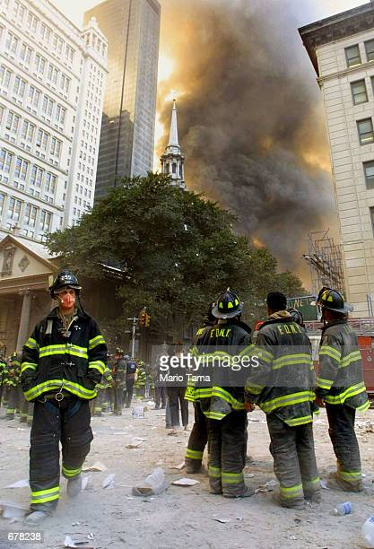 Firefighters watch as smoke rises from the site of the World Trade Center collapse September 11 2001 in New York City after two hijacked airplanes...