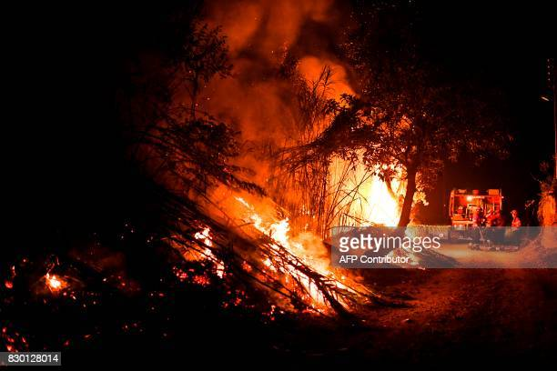 Firefighters watch the progression of a wildfire in the village of Aldeinha in Abrantes on August 10 2017 Firefighters aided by calmer winds were...