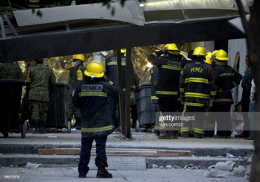 PEMEX firefighters watch the rubble at the headquarters of the state-owned Mexican oil giant Pemex in Mexico City on February 1, 2013, following a blast inside the building. An explosion rocked the skyscraper, leaving up to now 25 dead and 100 injured, as a plume of black smoke billowed from the 54-floor tower, according to official sources. AFP PHOTO/ YURI CORTEZ