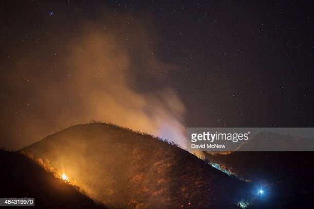 Firefighters wearing bluish LED headlamps climb to a hot spot under the stars at the Warm Fire on August 16 2015 in the Angeles National Forest north...
